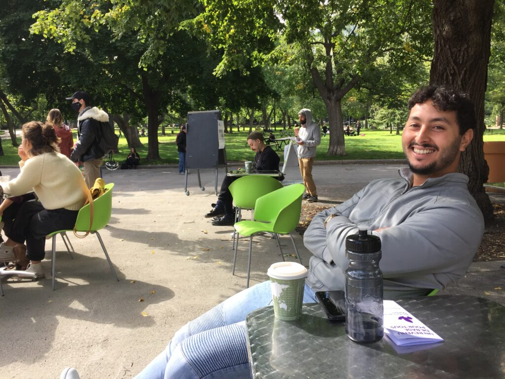 Younes attending the UBI informational gathering at Espace Lafontaine on Saturday September 19th 2020. Young man of Maghrebian descent with tousled black hair and trimmed black beard, sitting while leaning back with his arms crossed over a gray leather jacket, smiling widely at the camera.